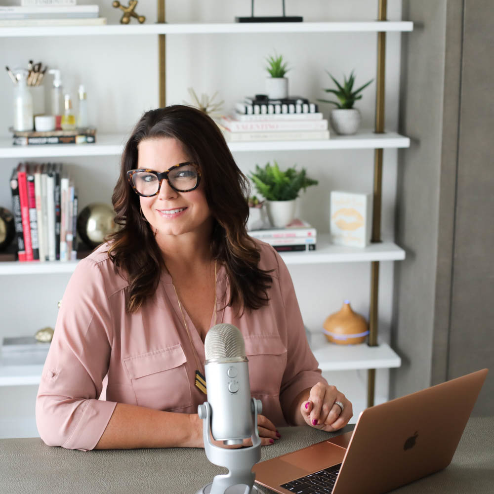 Glossible founder, Sonia Roselli, smiles sitting at desk in beautiful office with podcasting microphone and laptop in front of her