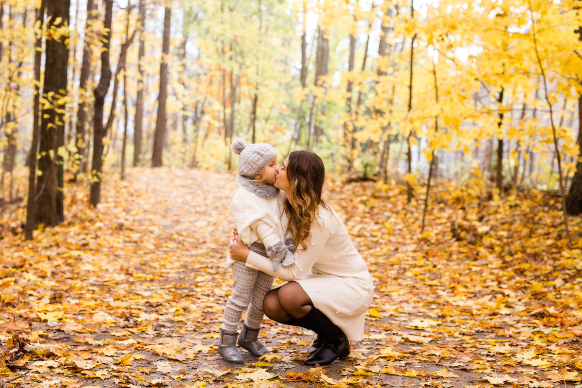 Mother kissing toddler daughter in woods {Oakville Family Photographer}