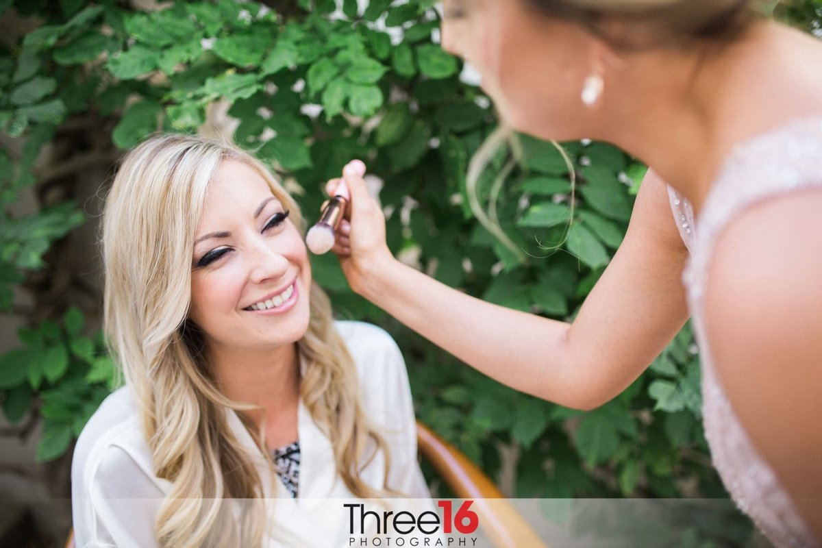 Mother of the Bride applies final makeup touch to her daughter