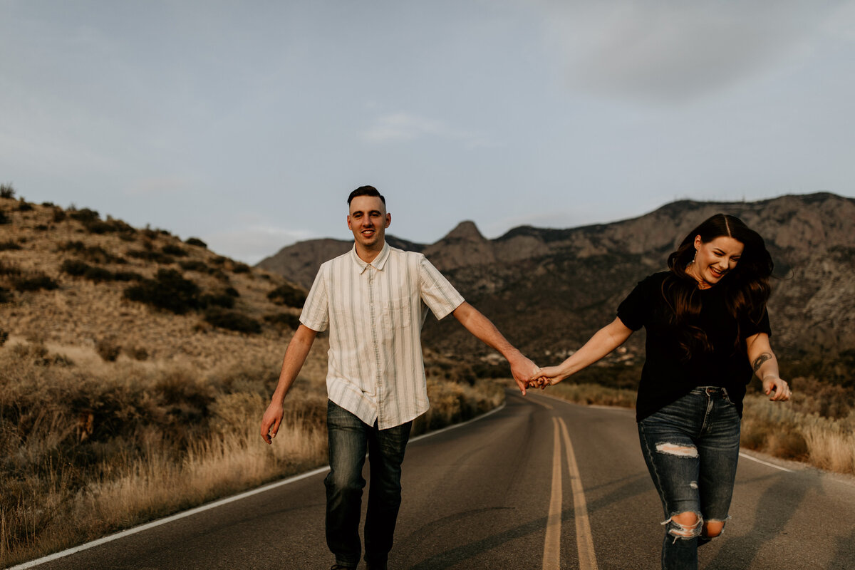 engaged couple holding hands and running in the road