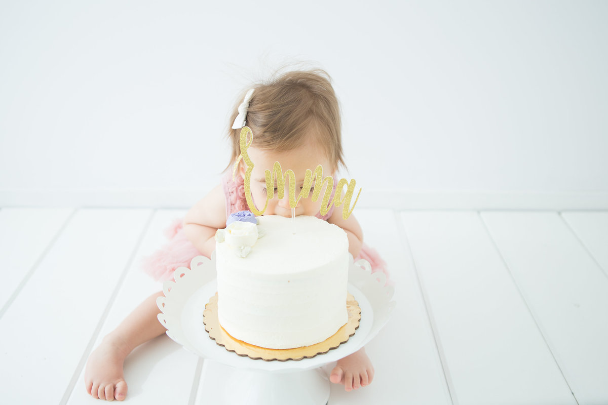 baby girl taking a bite of her birthday cake {Hamilton Baby Photographer}