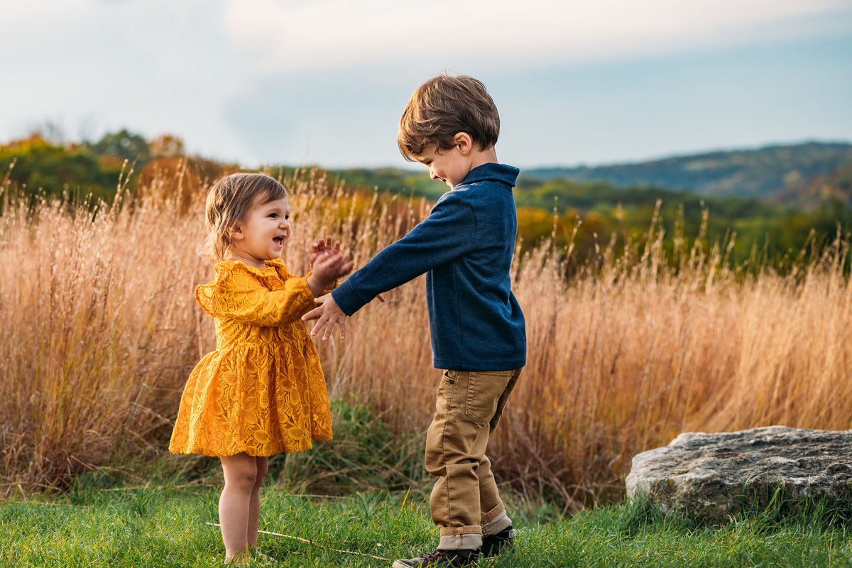 Siblings playing in grass McKenna Patterson Photography Madison WI