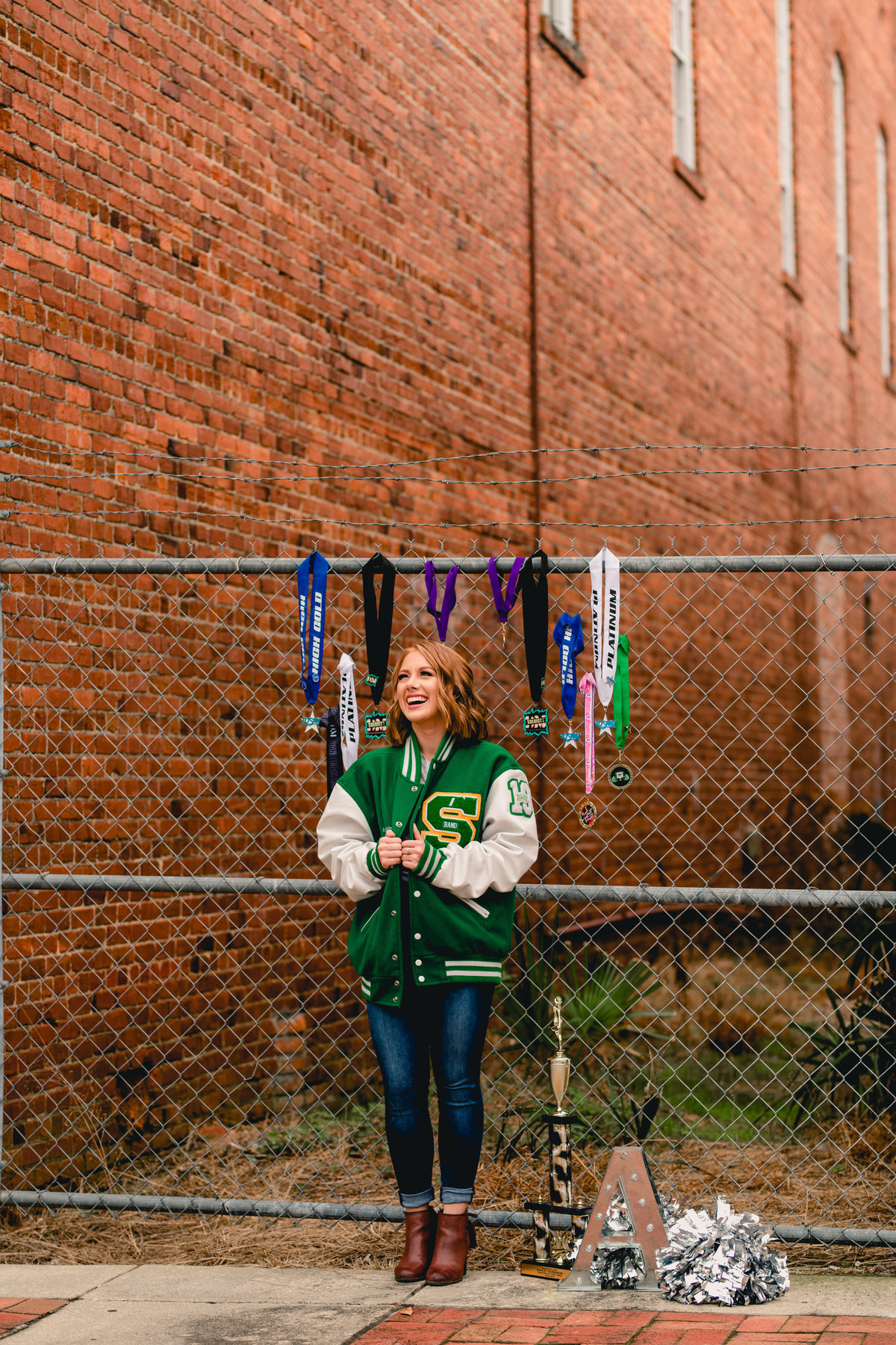 Senior portrait session including medals from sports and letterman jacket in north florida.