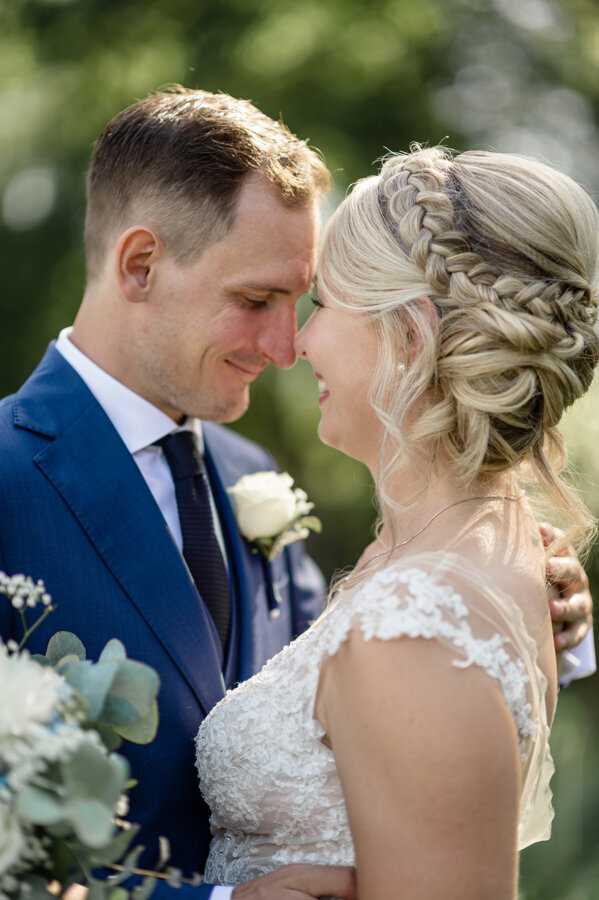 Close up of bride with loose up do and braid looking at her groom and smiling