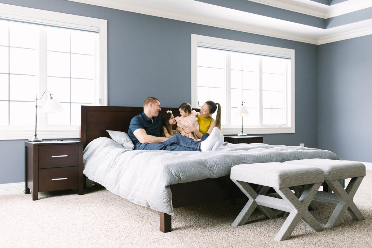 Family of four sitting on a bed