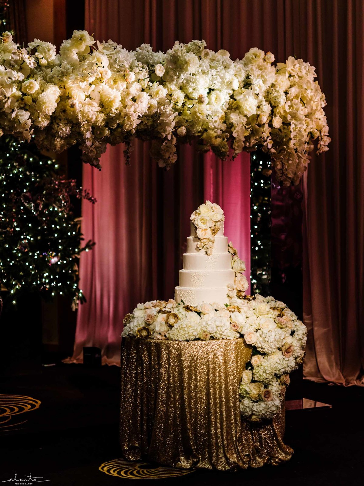 Wedding cake surrounded by white floral cascading over the cake table.
