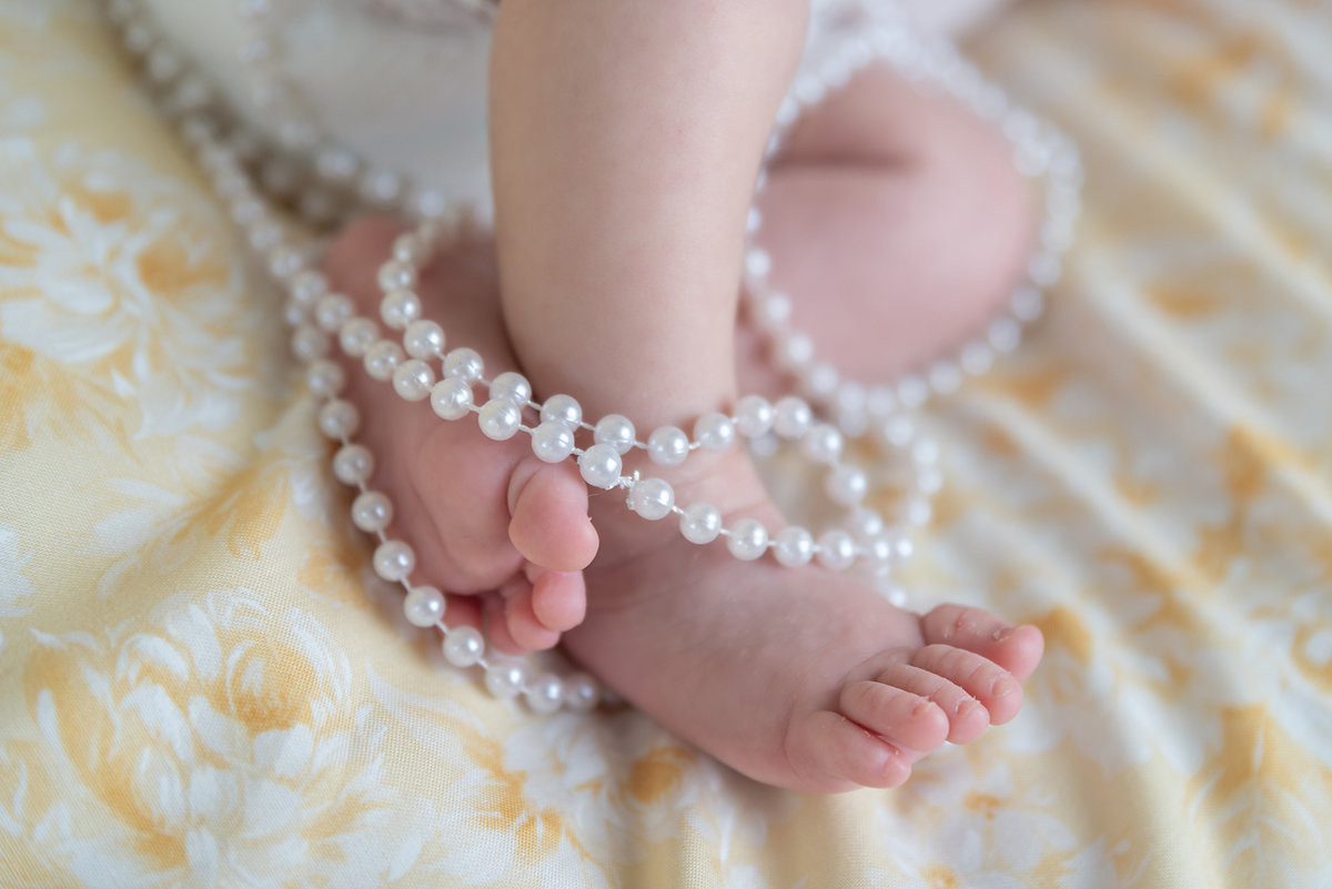 image of a newborn baby's feet wrapped in pearls