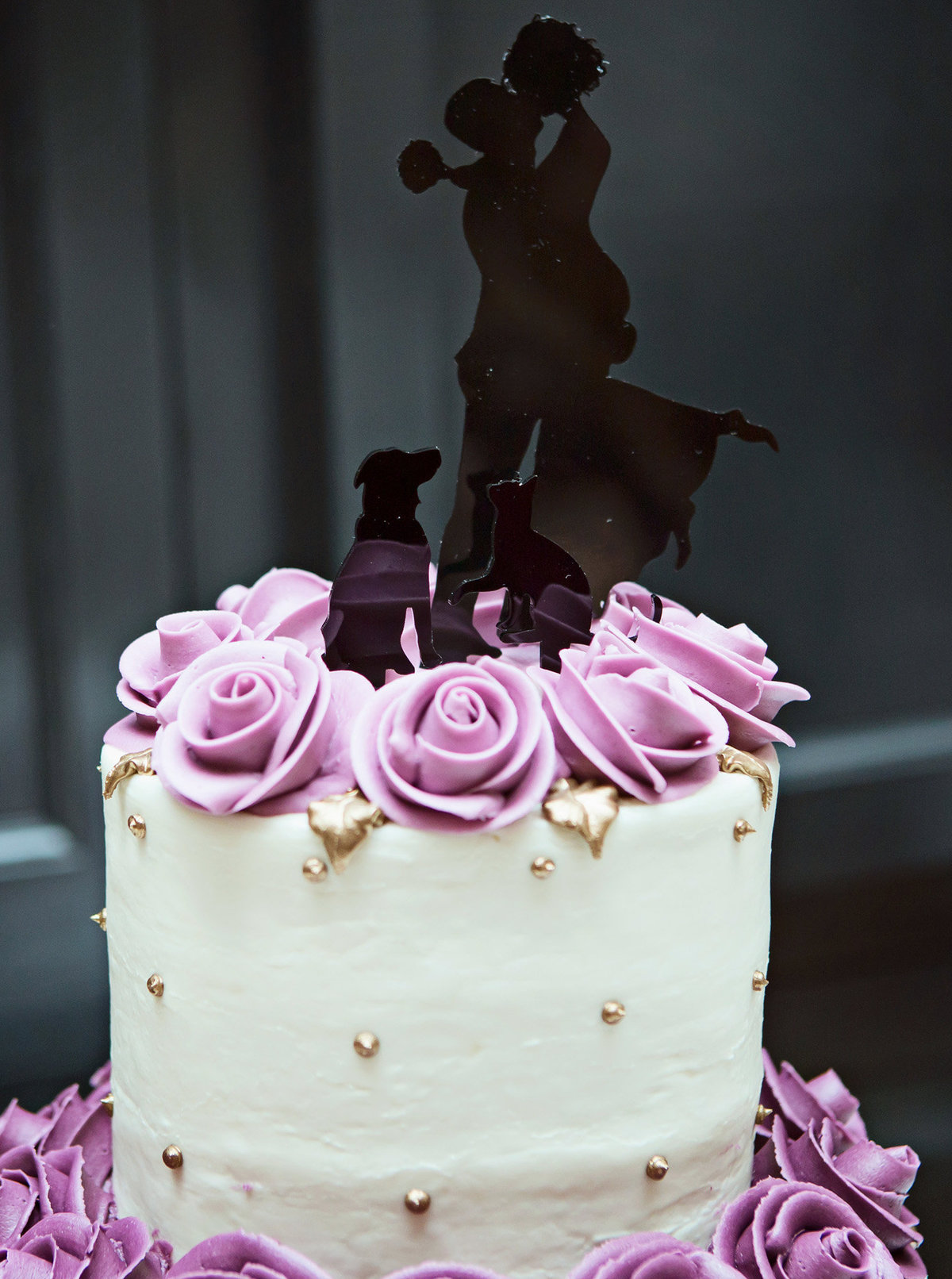 cream wedding cake with lavender flowers and black cake top in the Count's Ballroom of Arnaud's Restaurant