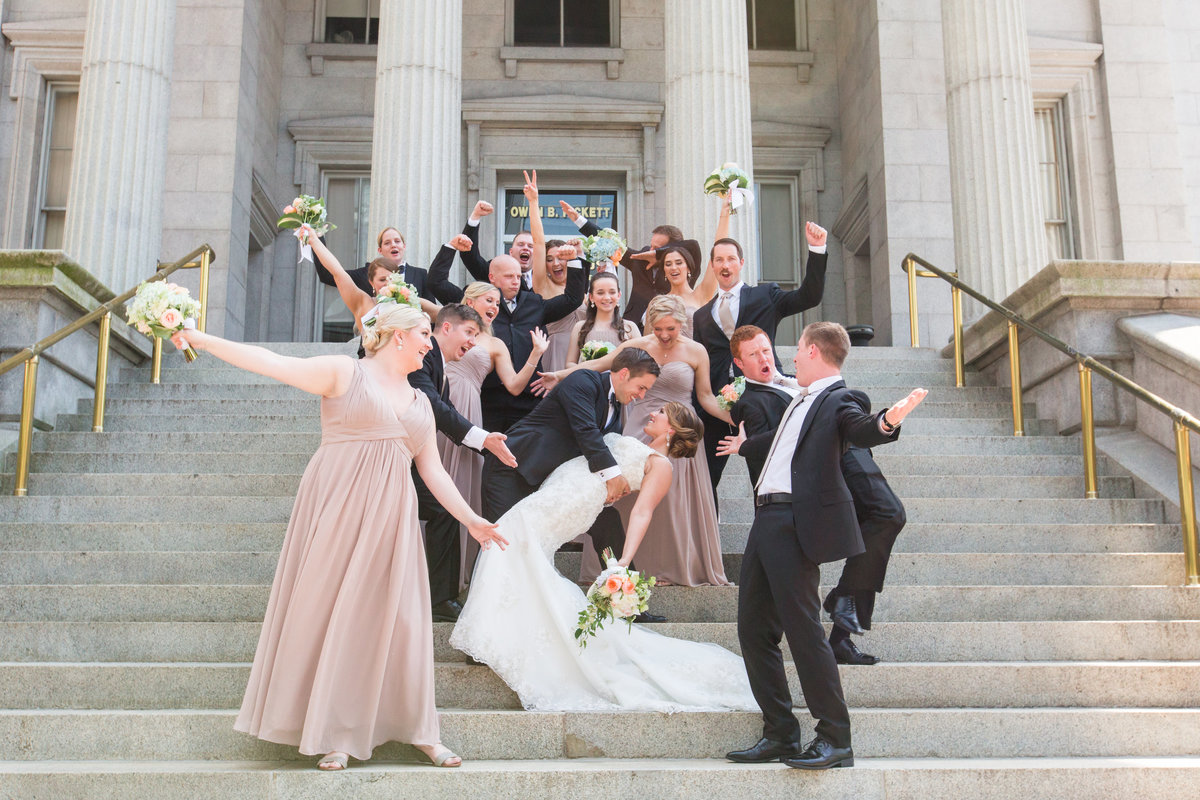 bridal party having fun on the steps of the Customs Building in Norfolk, VA