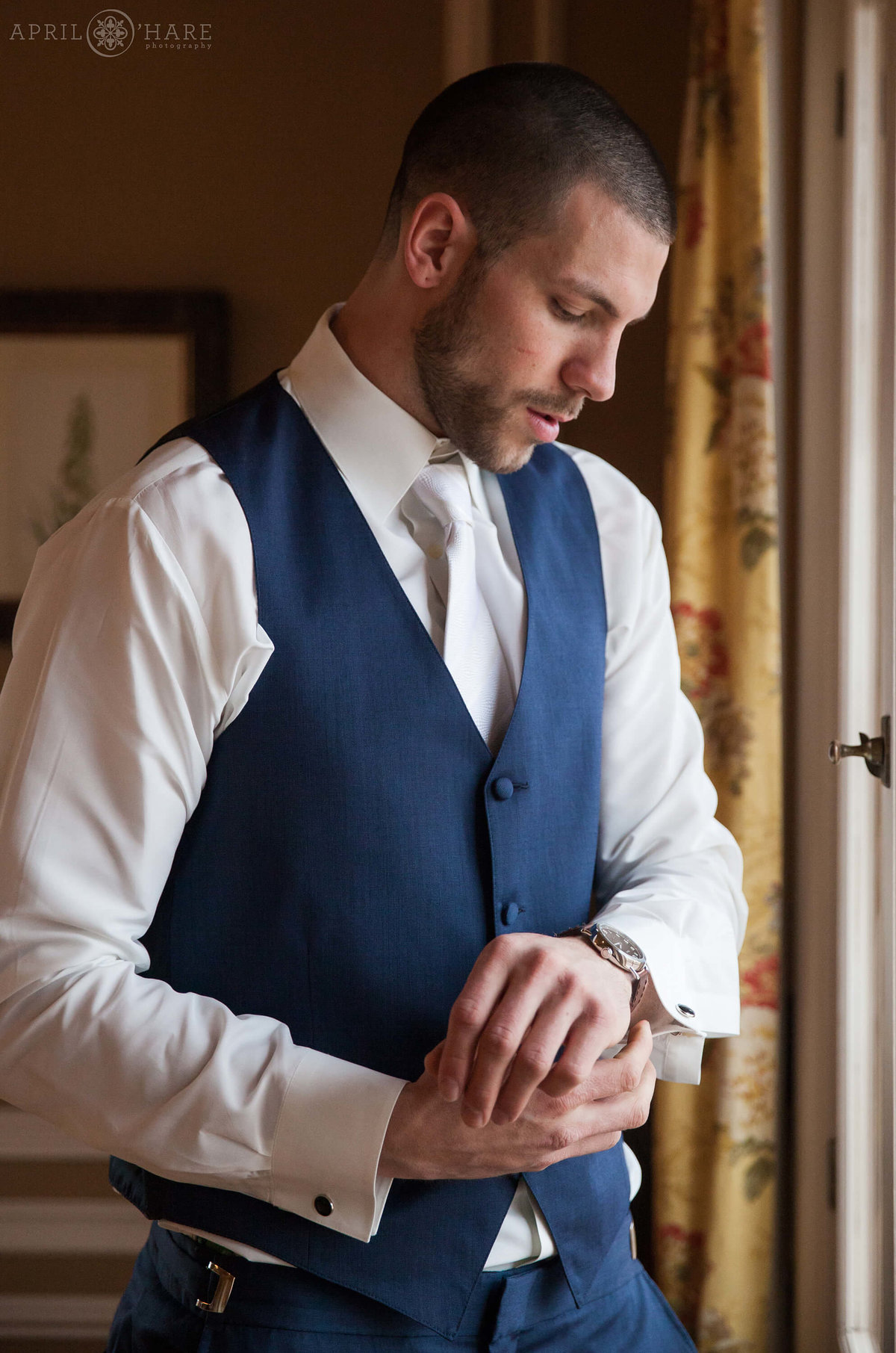 Groom dresses for wedding day at Highlands Ranch Mansion in Colorado