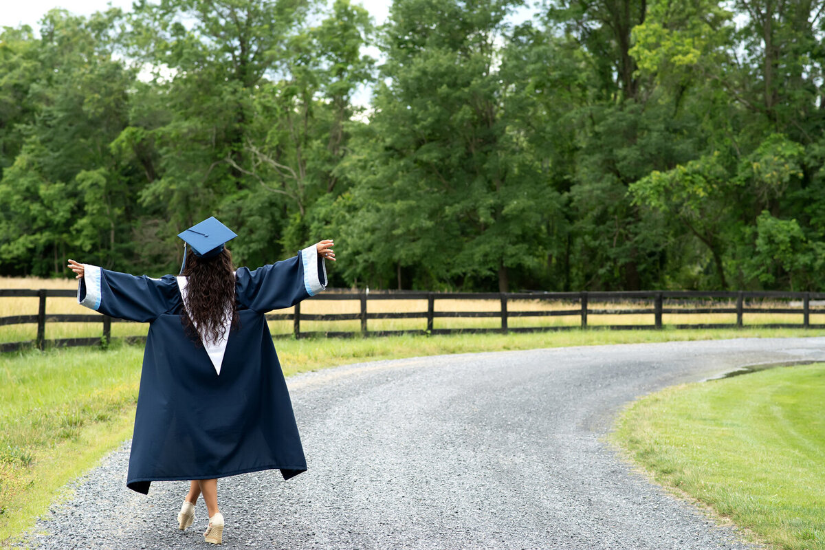 senior girl cap and gown country road walk away photo