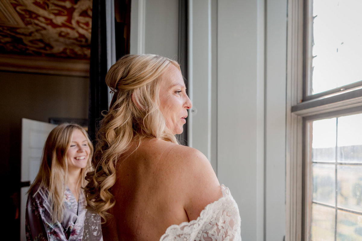 Bride by the window getting help with her dress