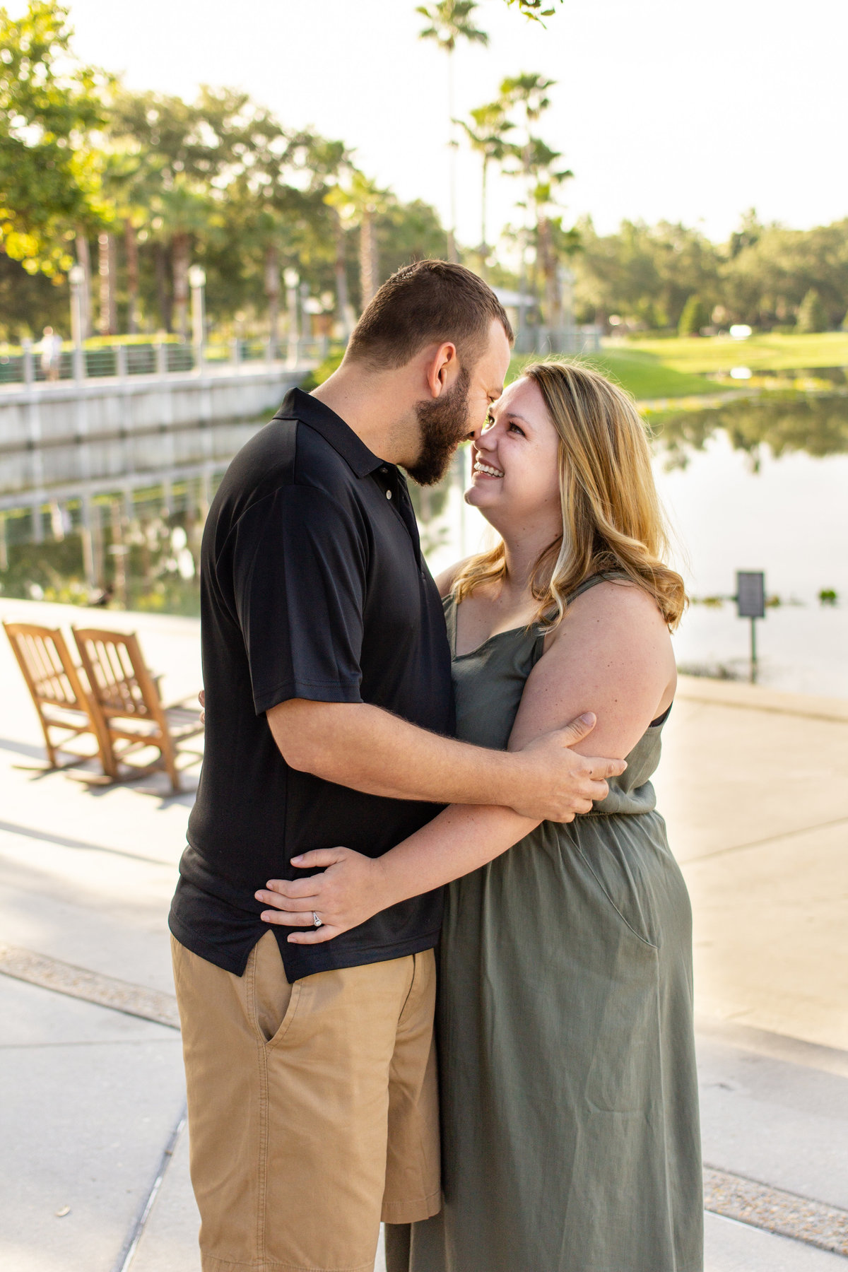 Couple smiles at each other during their sunrise engagement photo session in Celebration, Florida