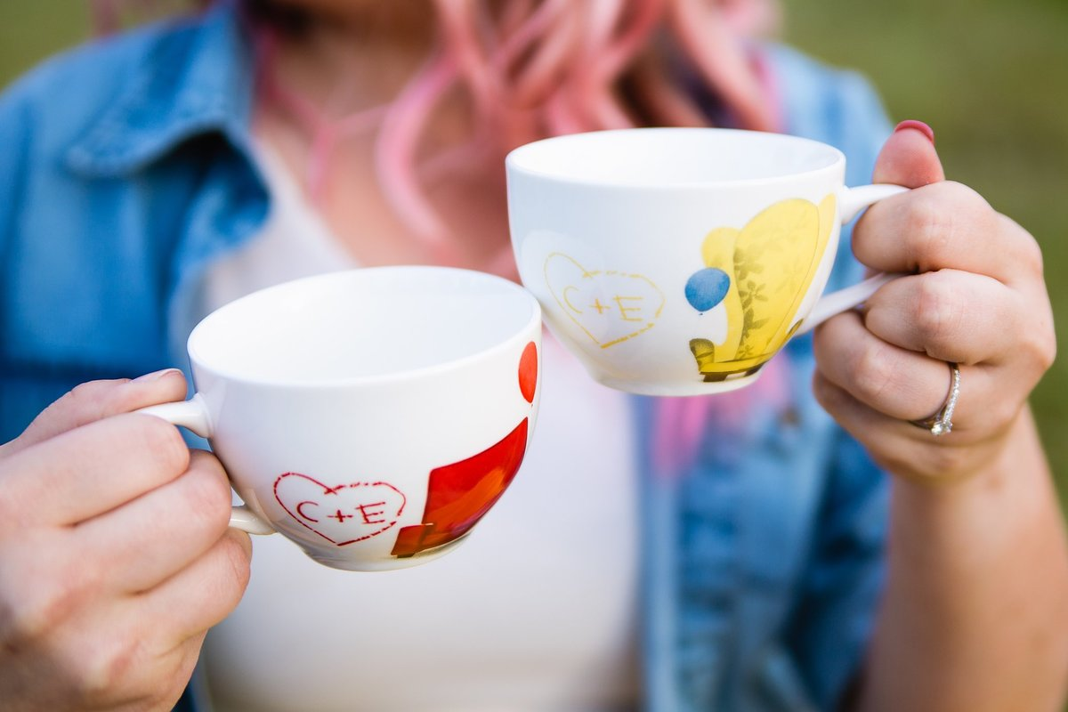Couple toasting with Up tea cups during their picnic engagement session by PMA Photography.