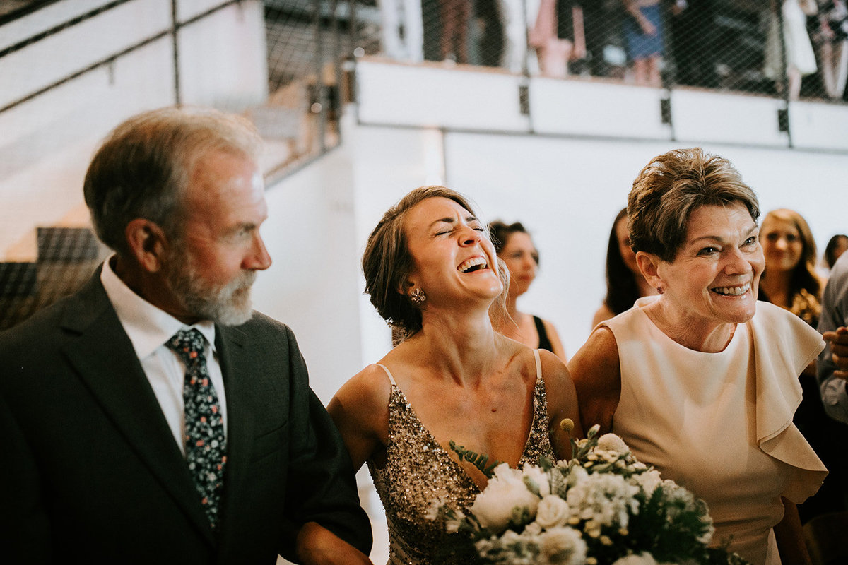A bride laughs with her parents arm in arm.