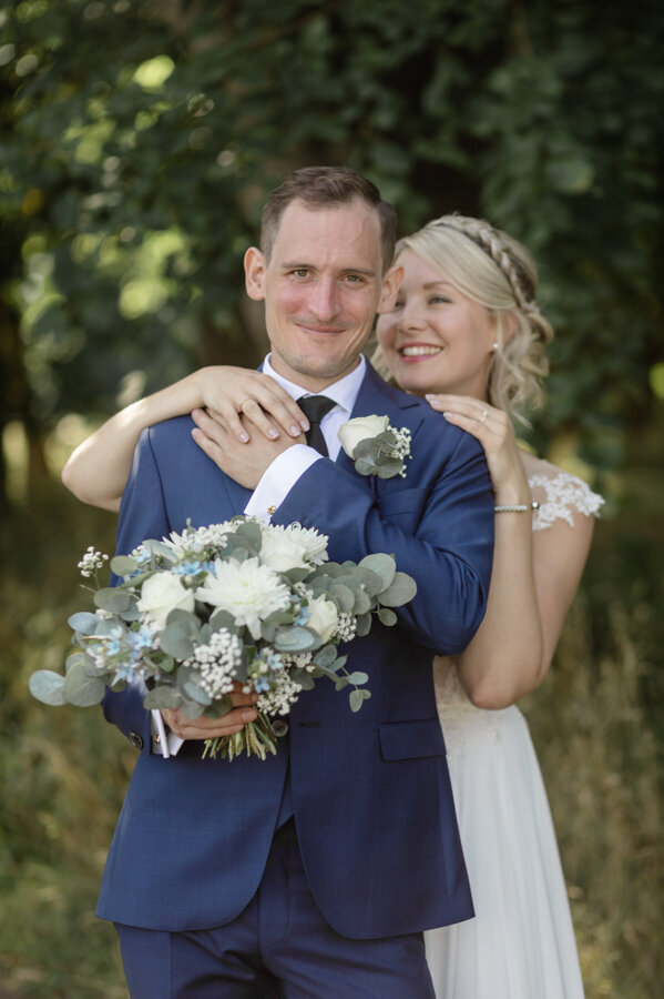 Groom in navy suit and white and green lapel flower stands outdoors and looks into the camera as his bride caresses him from behind