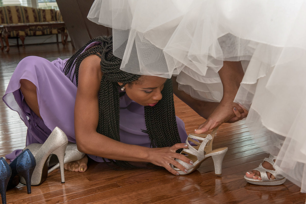 Bridesmaid helping with shoes on the bride