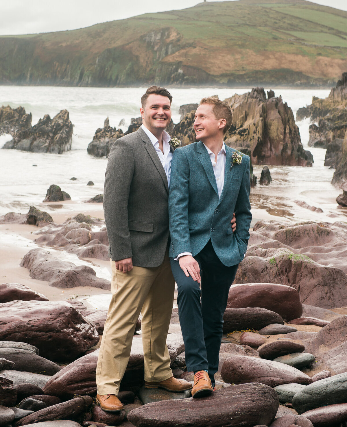 Two grooms standing on rocks looking at each other on beach