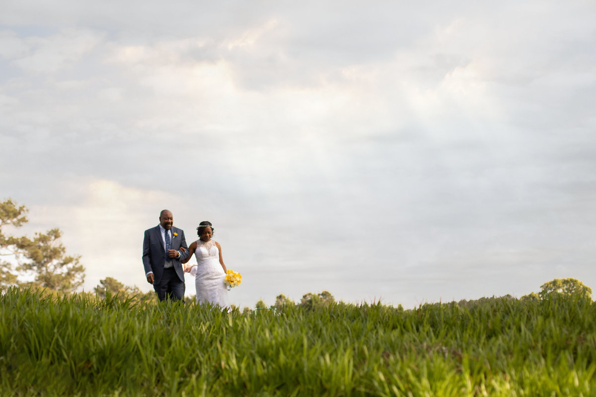Bride and Father on a grassy hill