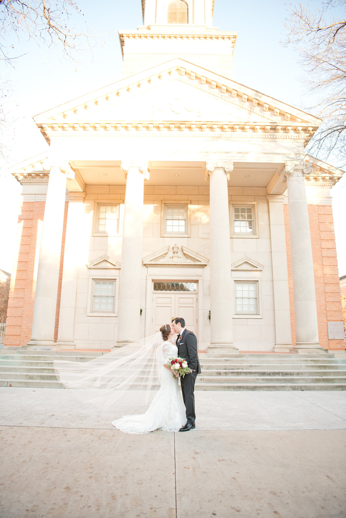 Bride and groom kiss with flowing veil at Robert Carr Chapel in Fort Worth Texas wedding