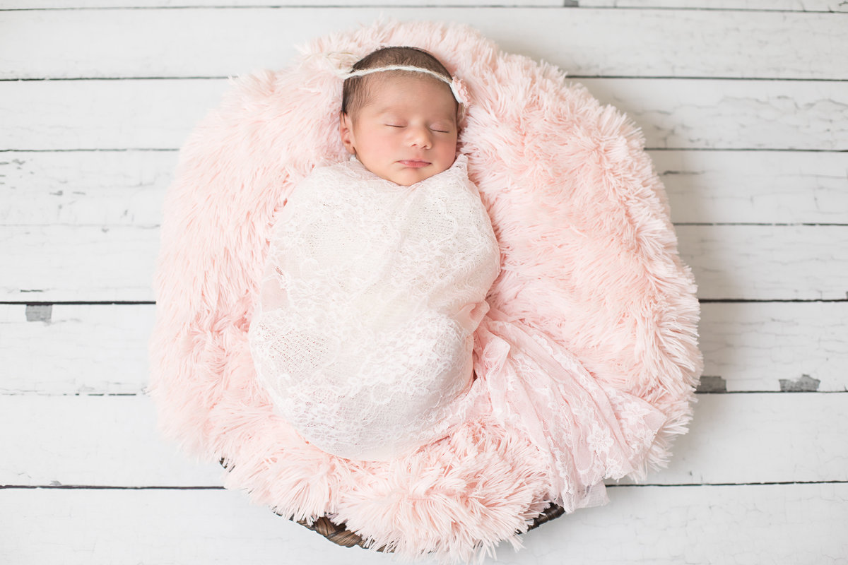 Sleeping newborn in pink lace and pink blanket