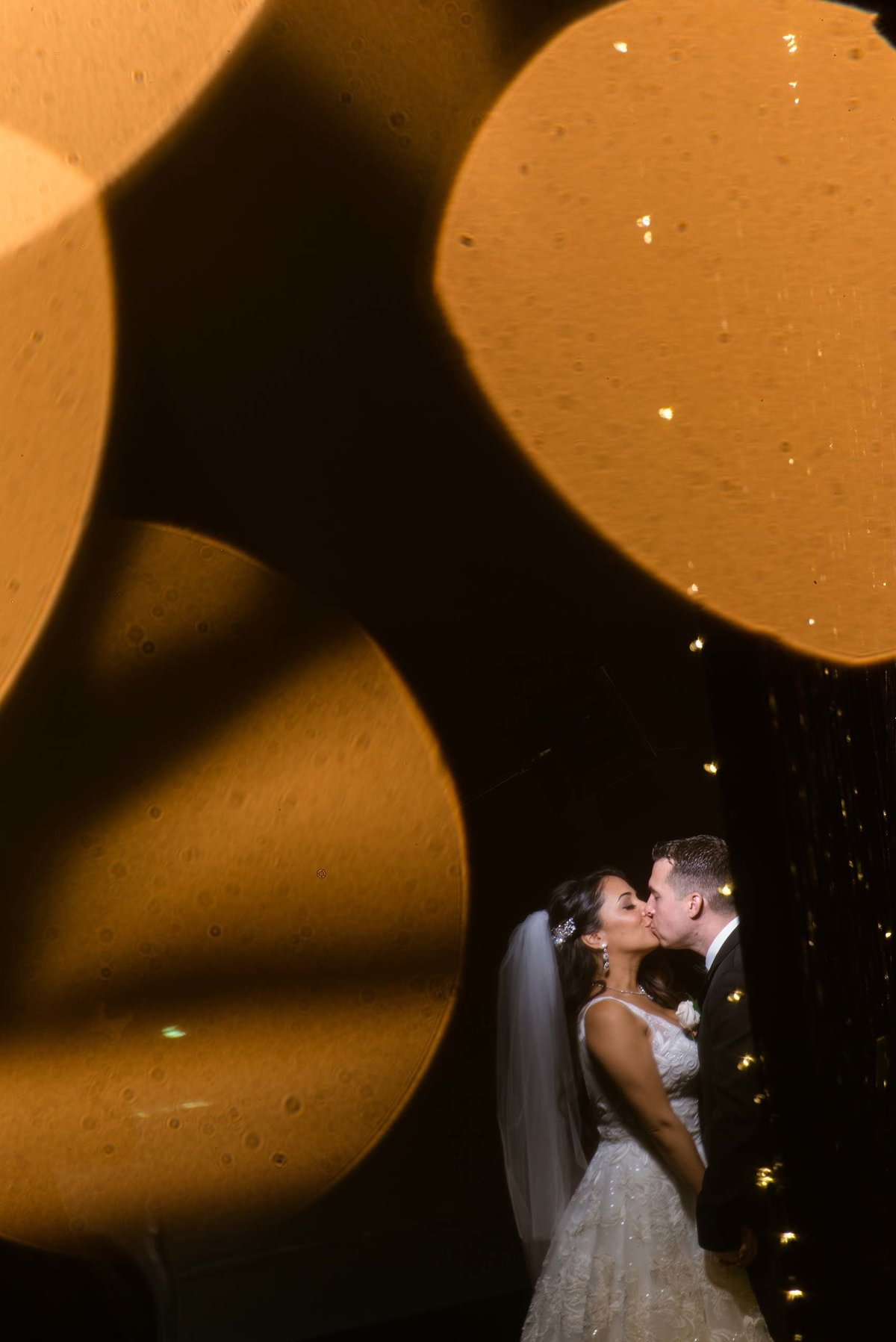 Bokeh photo of bride and groom kissing at Fox Hollow