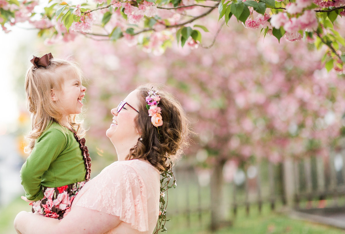 Mother and her young daughter pose with the cherry blossom trees