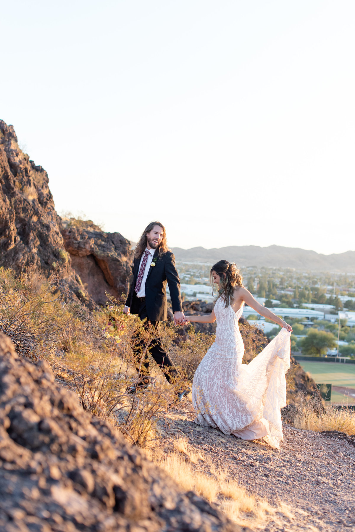 groom leads bride up mountain in phoenix arizona