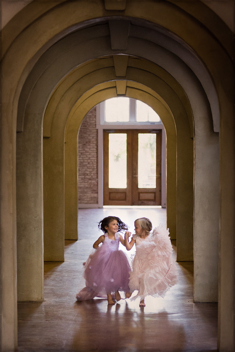 Two little girls wearing fancy gowns in pink and purple hold hands, laugh, and smile while running down hallway of Sky 9 Studio.