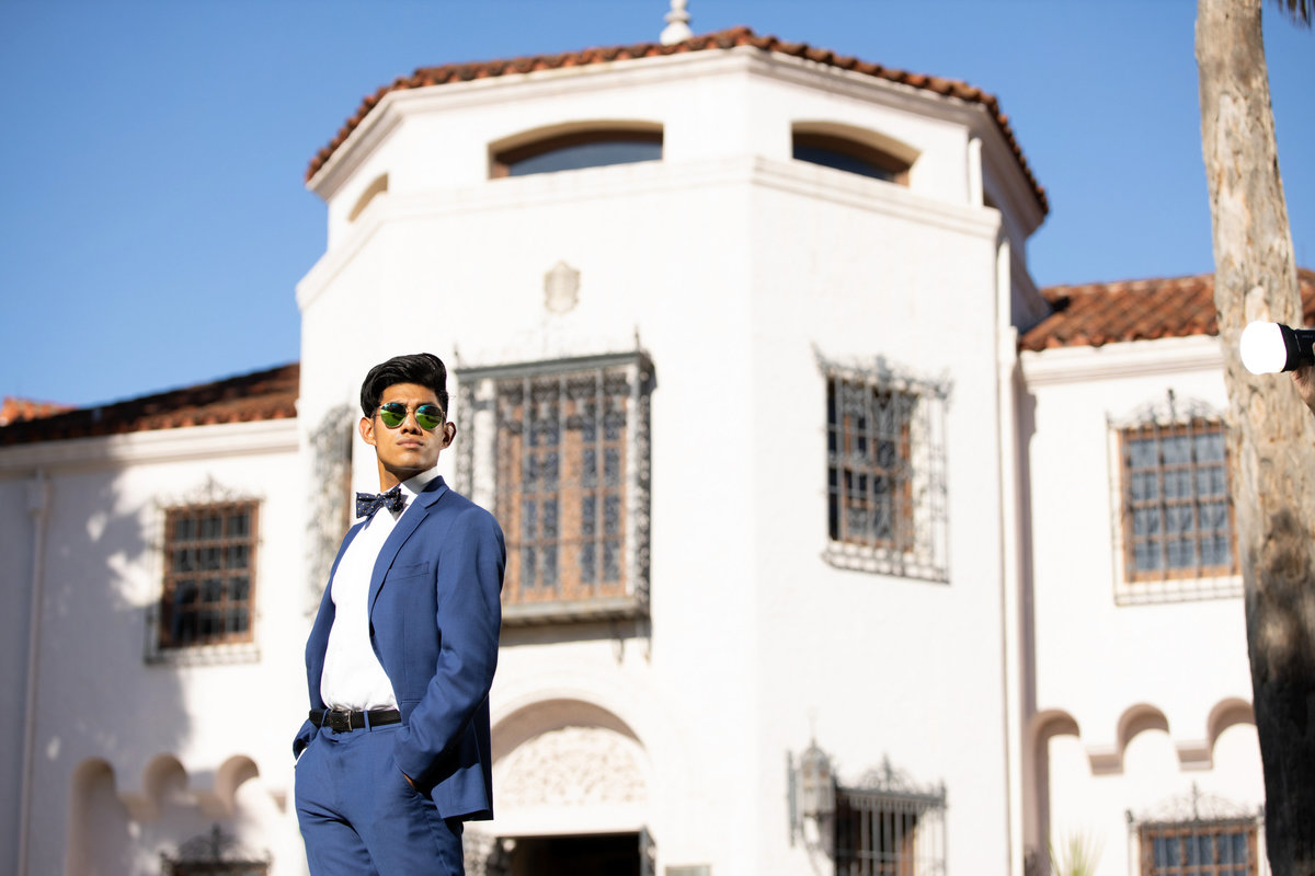Senior boy in blue suite with sunglasses infront of white building.