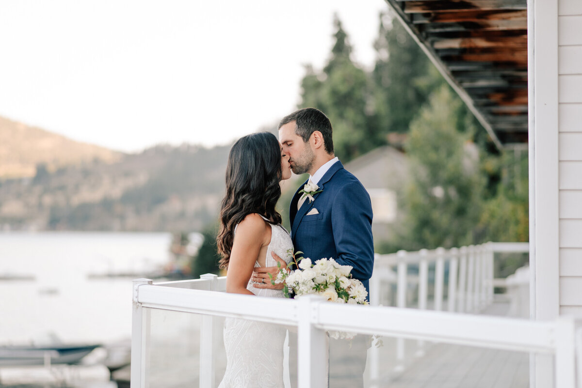 Bride and groom kissing on balcony at Lake Chelan Airbnb