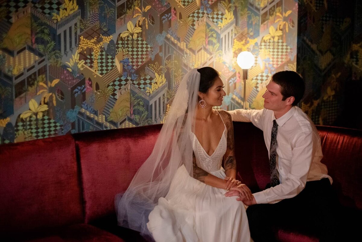 a bride and groom have a moment sitting on a red velvet couch in front of a colorful fun wall in Voysey speakeasy