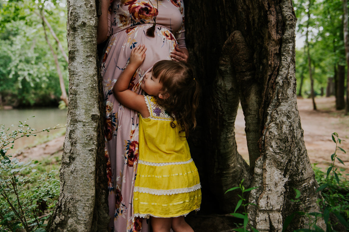 child in yellow dress hugging pregnant mom