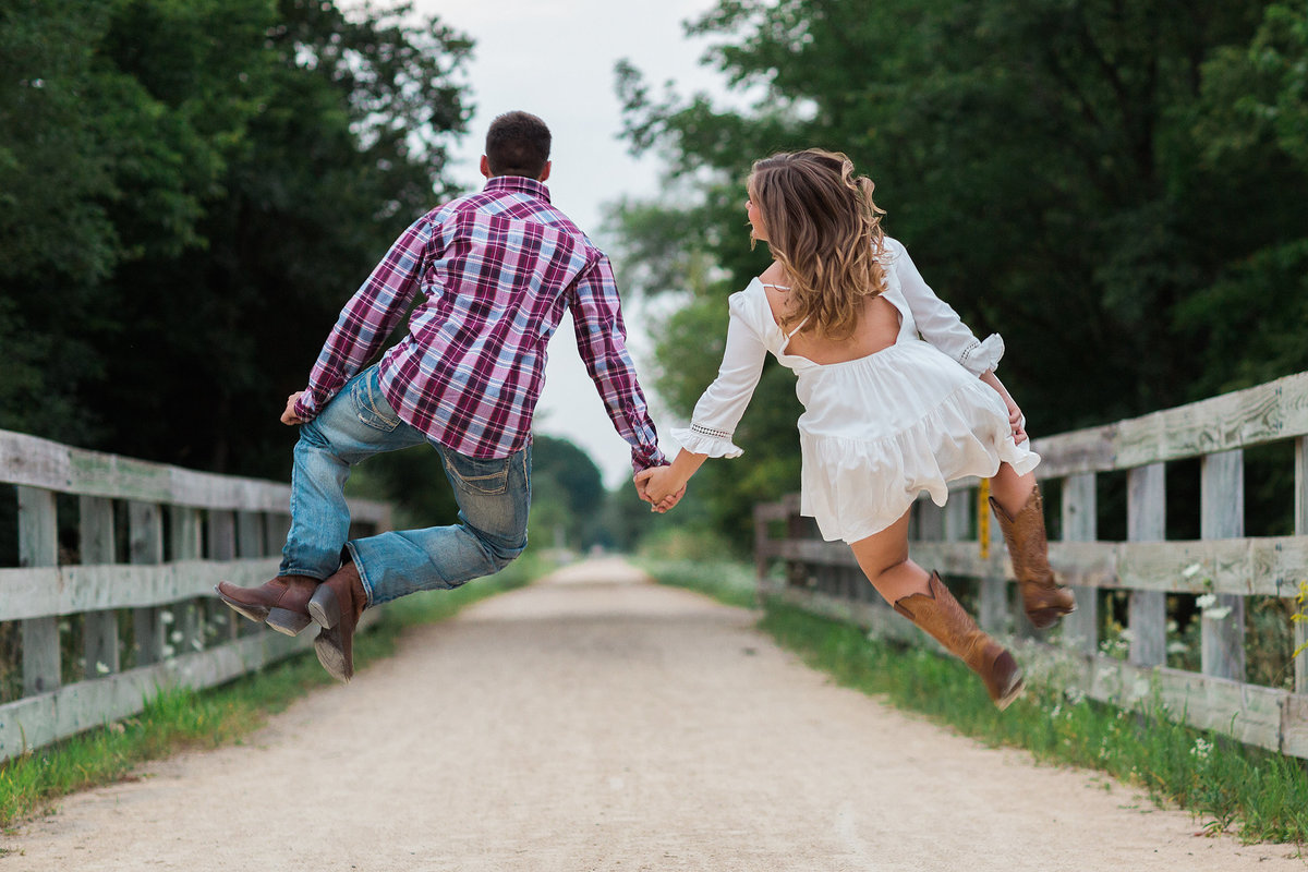 engagement photograph of couple jumping up and clicking heels together