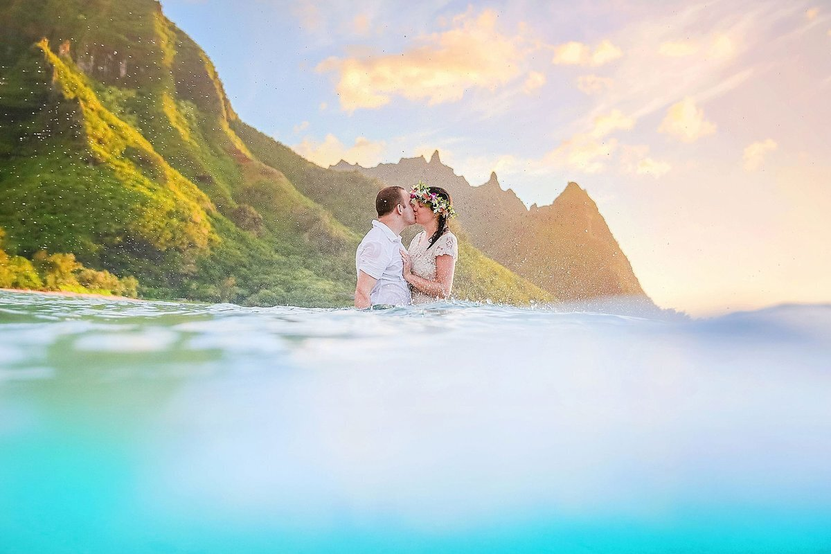 Engaged couple on Kauai kissing with Ke'e Beach in the background