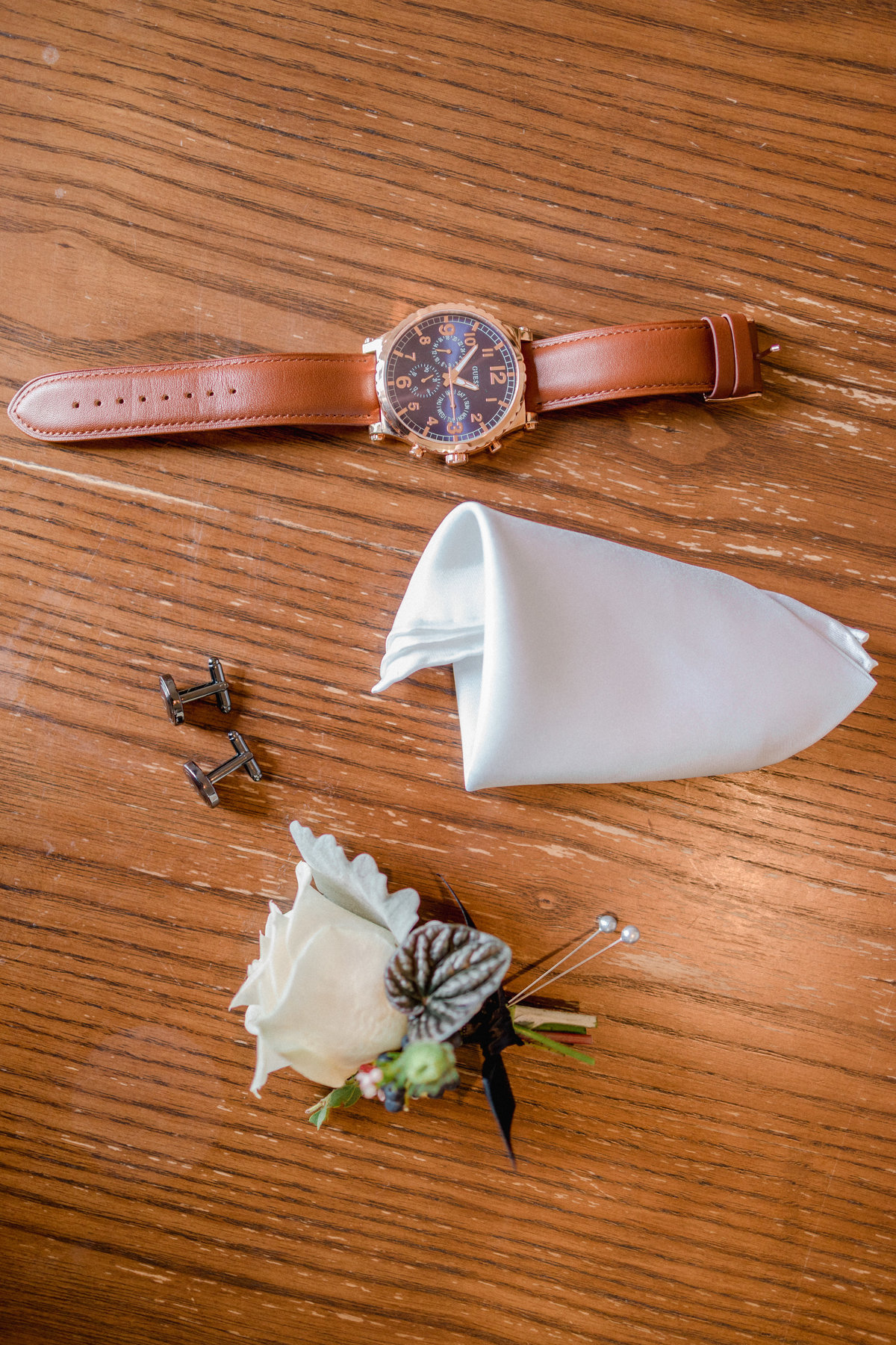 brown watch, silk white hankerchief and cufflinks with rose on wooden table