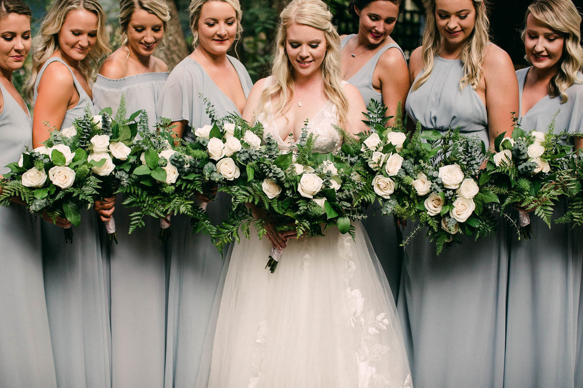 Dusty blue bridesmaids and ivory flowers