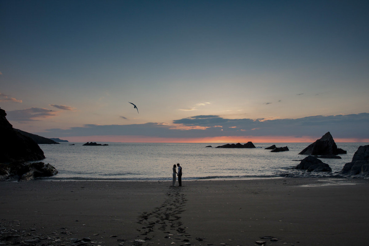 Beautiful sunset wedding photo of Bride and Groom on Beach at Tunnels Beaches