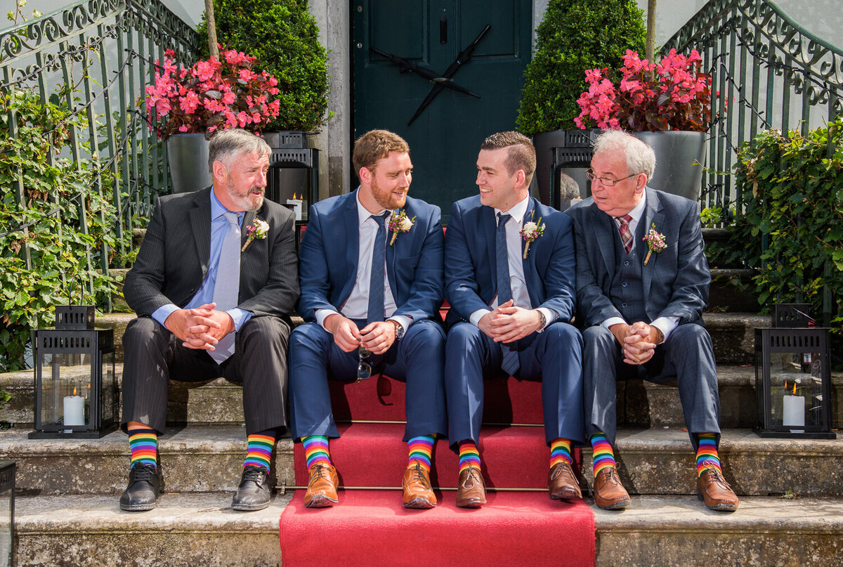 fathers sitting with groomsmen on a step with red carpet and wearing rainbow socks