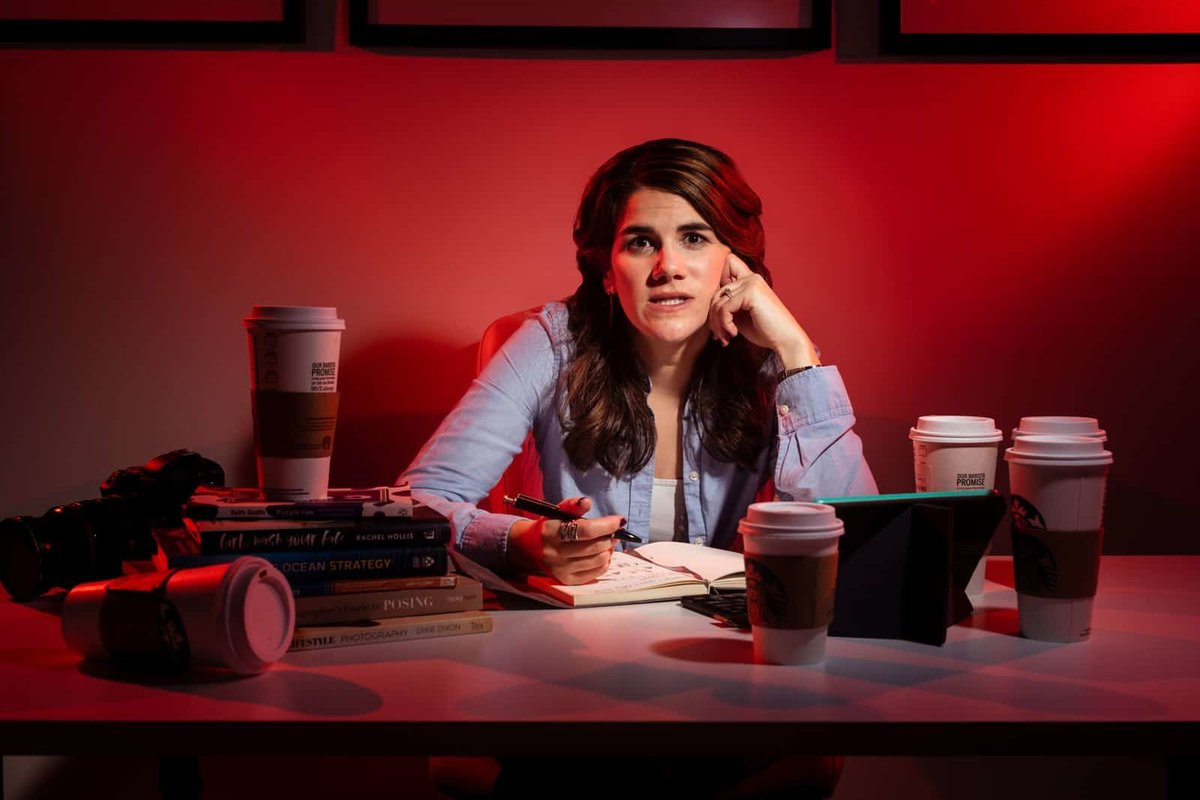 stressed out female freelancer surrounded by empty starbucks coffee mugs at desk