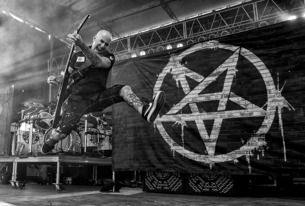 Scott Ian of Anthrax jumping with guitar in front of pentagram