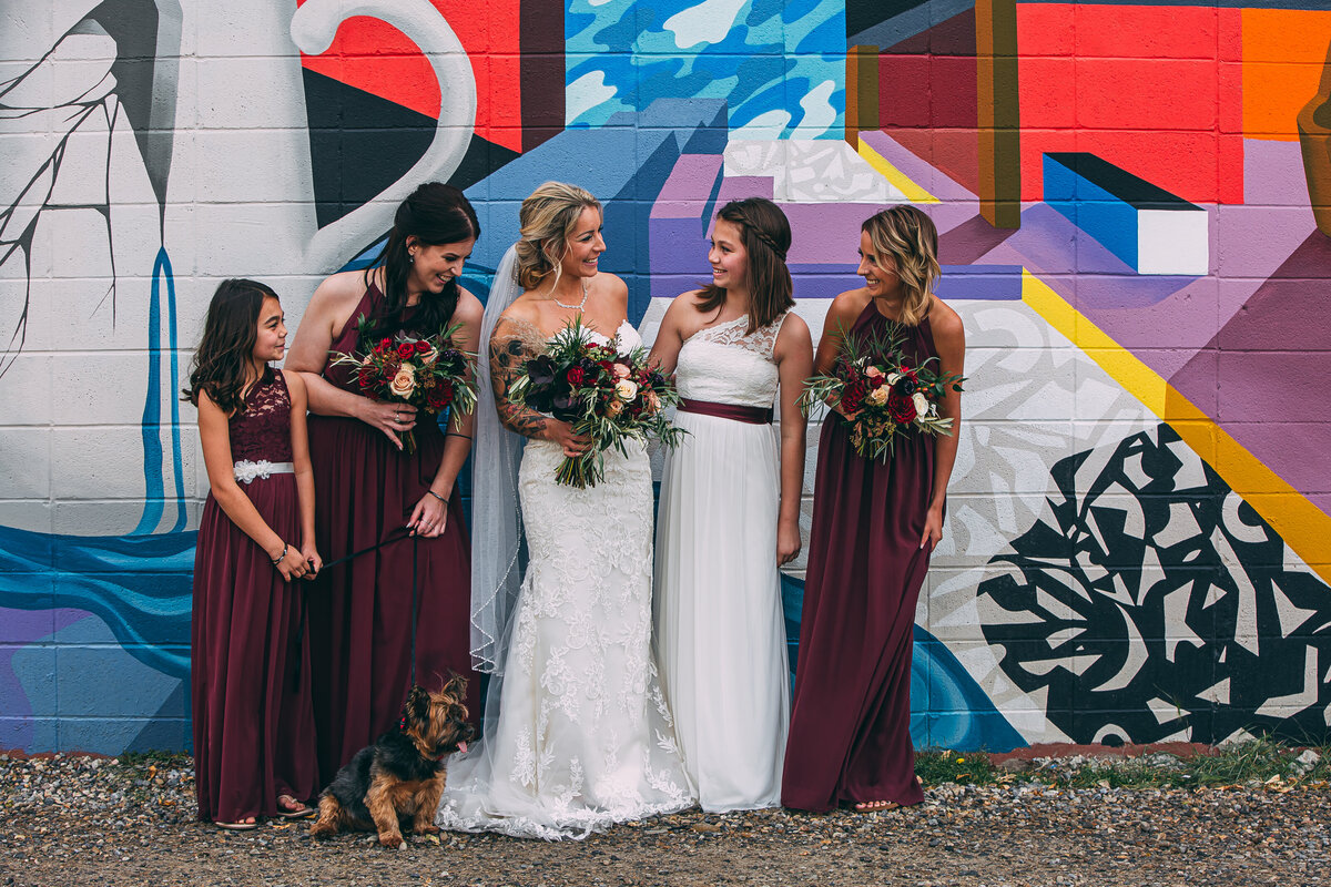white and burgundy bridal party stand together in front of graffiti wall.