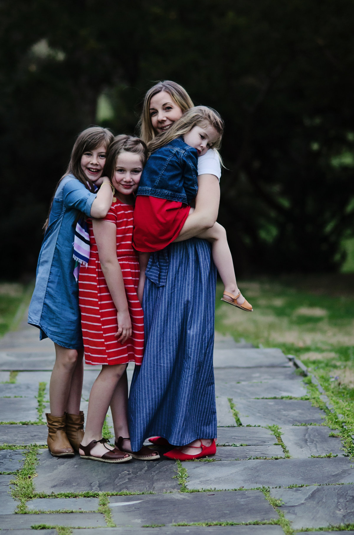 Portrait of a Mom and her three daughters hugging at Glenview Mansion in Rockville, Maryland taken by Sarah Alice Photography