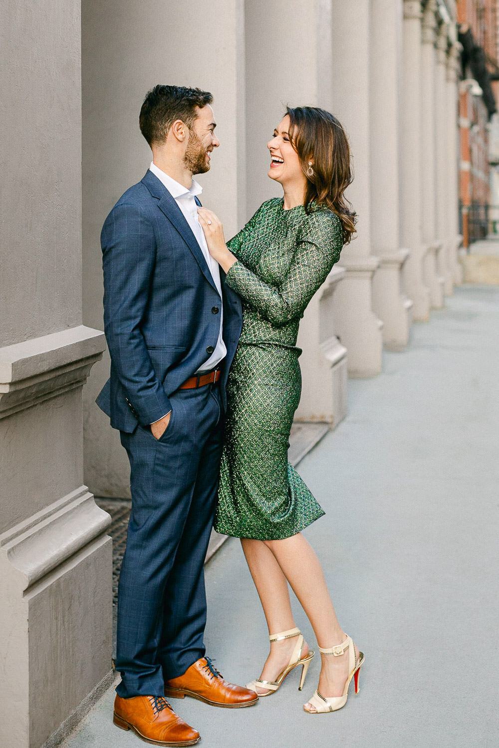Man in blue suit and woman in green dress standing together in Tribeca NYC street