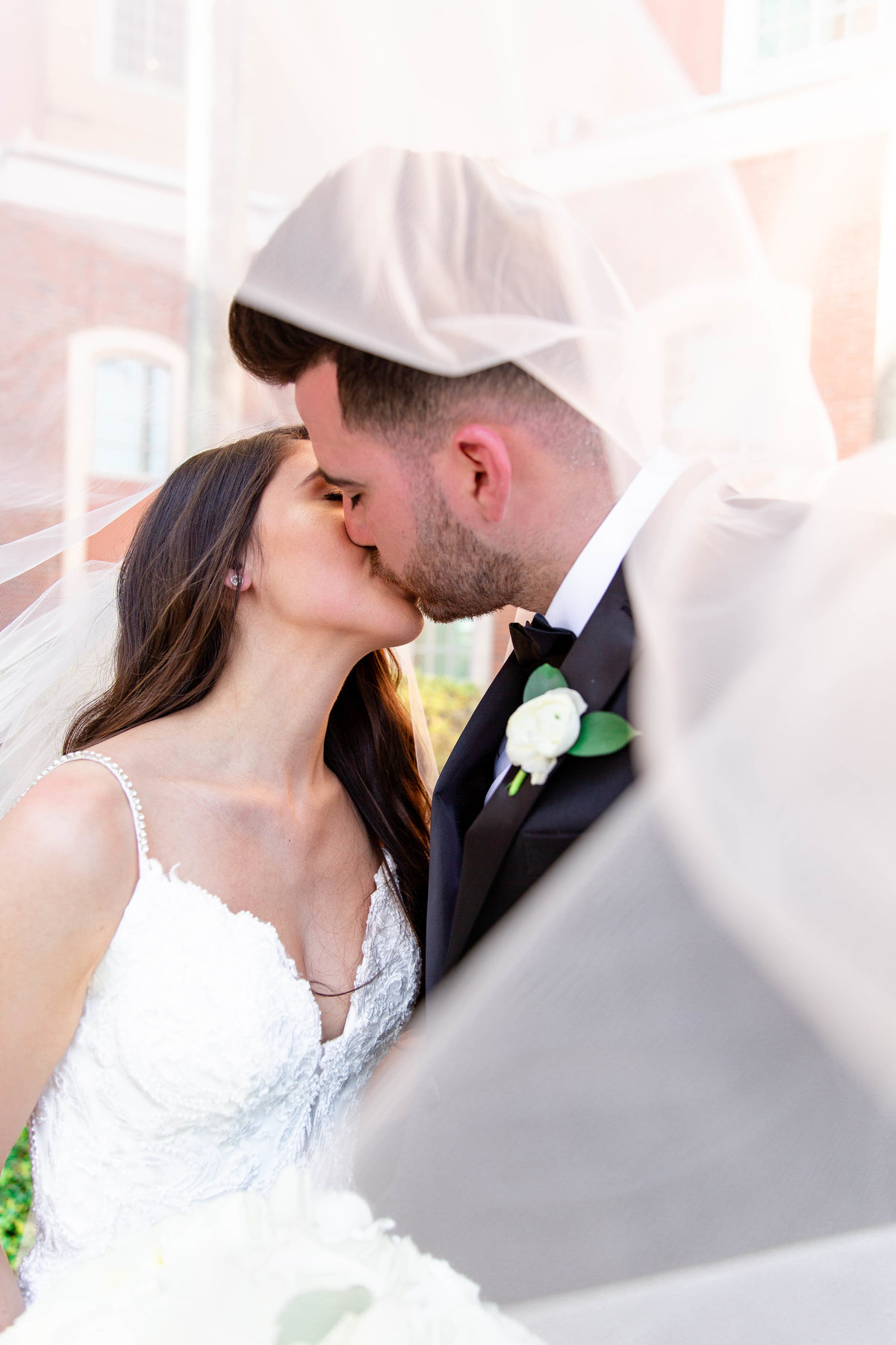 Bride and groom kiss on wedding day under veil in black tie wedding attire