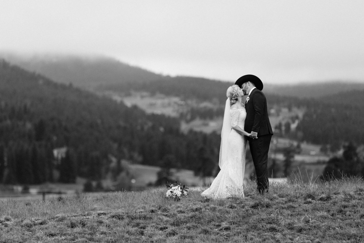 A newlywed couple kissing with fog in the background.