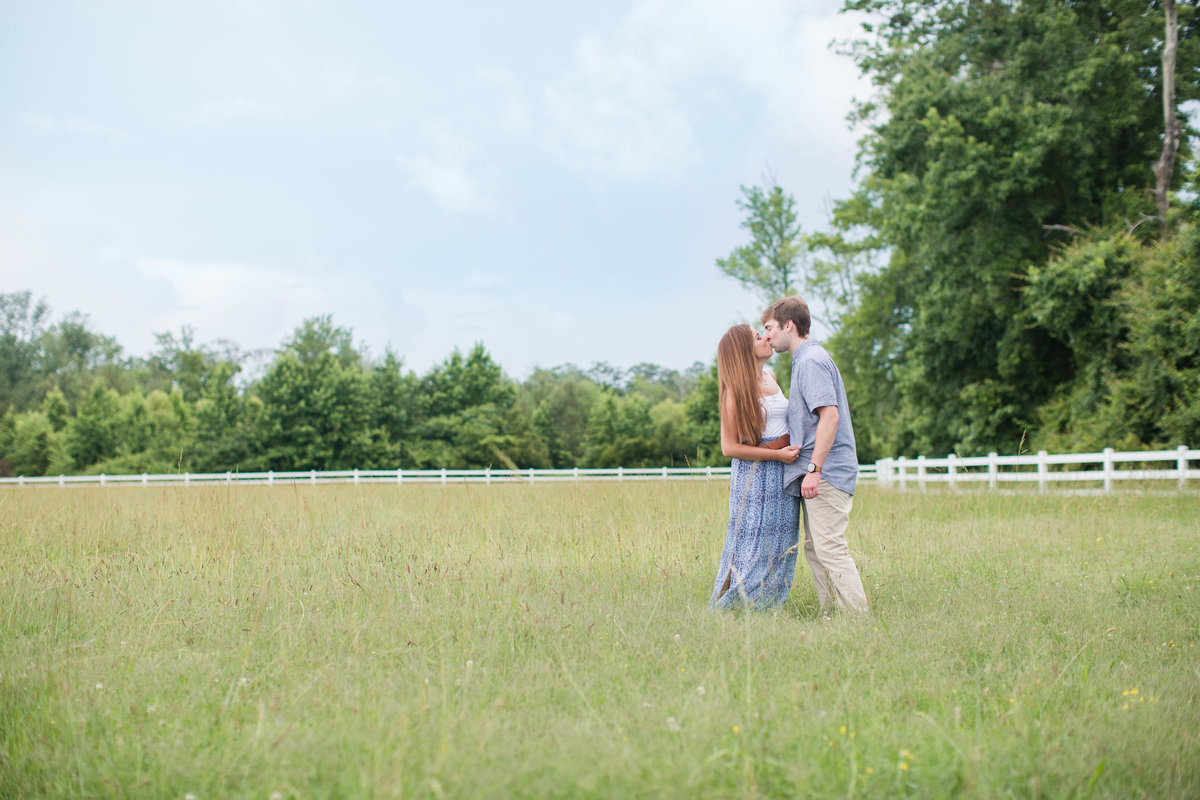 couple kissing in a field for engagement session in virginia beach