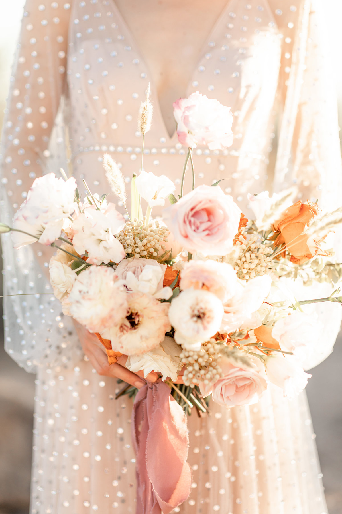 peach and cream bridal bouquet with pink ribbon and gorgeous ivory wedding gown in desert inspired wedding