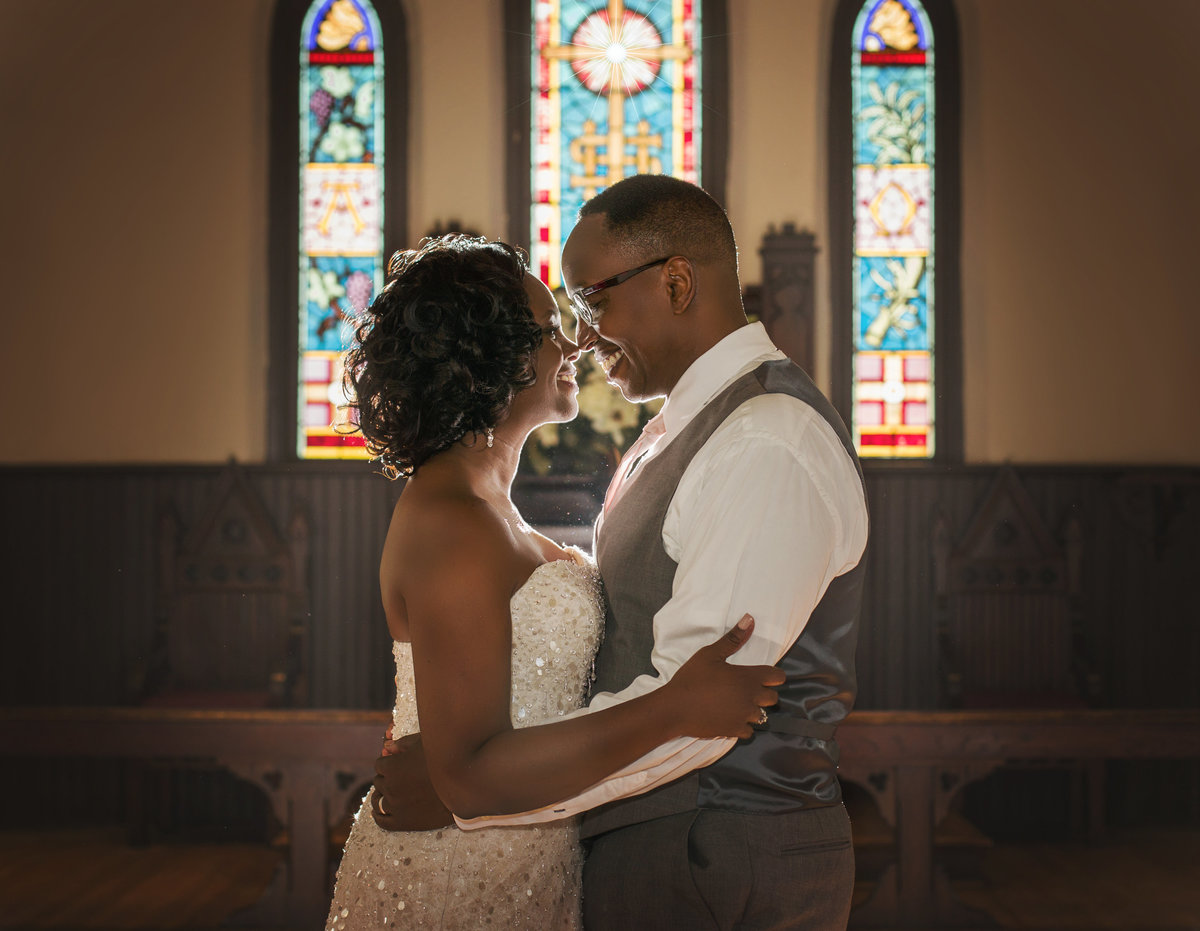 charlotte wedding photographer jamie lucido captures image of bride and groom just married in front of stained glass windows at St. Mary's Chapel in Charlotte, NC