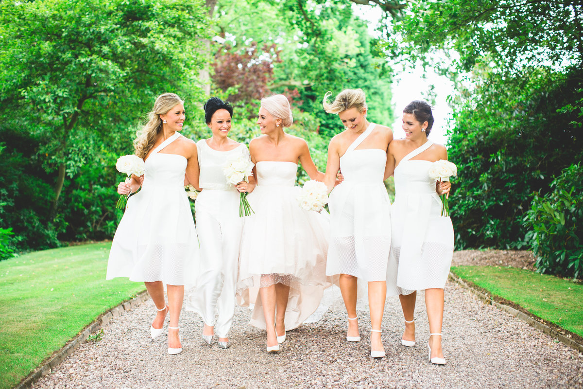 bridal party photo all in white walking and laughing